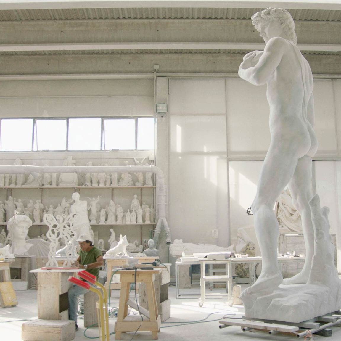 A sculptor carves David statues from Carrara marble in Italy. A detail from a film still from Anthropocene: The Human Epoch